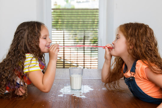 Little girls playing with straws over glass of milk