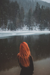 Handsome redhead girl looking in the distance. Snowflakes falling on her hair. Splendid shady black mountain lake. Dreamy winter landscape of Carpathian mountains. Look from behind
