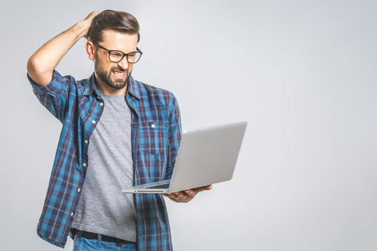 An amazed young man has got a software error. Isolated on grey background.