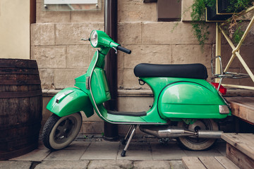 Retro style green scooter on Lviv street. Exterior, restaurant design. Modep left outdoors