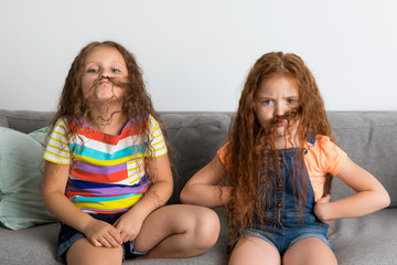 Young girls making fake mustache with their hair