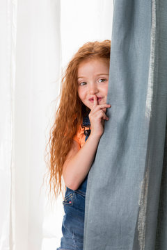 Redhead girl with finger on mouth hiding behind curtain