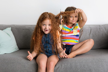 Little girl on sofa cutting her friend's hair with cisors