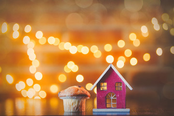 Homemade classic cupcake and wooden toy home with fairy lights in bokeh.