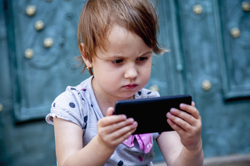 Social Media addiction. Little child girl holding smart phone (psychological problems, media mania, education concept)