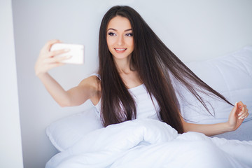 Shot of Happy cute woman lies on bed using mobile phone