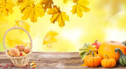 pile of orange pumpkins with basket of mashrooms on wooden table over fall background banner