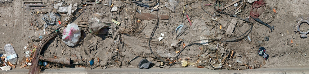 Panorama of dirt and trash in a gutter.