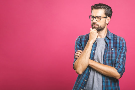 Portrait of unhappy determined european male with bristle touching chin while thinking and looking with serious and worried look at camera, standing against pink background.