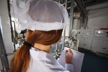 beautiful young girl in white working clothes is making a note on paper against the background of factory equipment