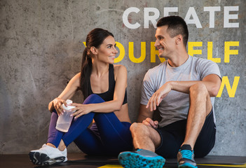 Positive guy is coGrinning couple is relaxing and sitting on floor in sport center after workout. They are having pleasure while chatting and resting. Woman is holding flask with water for quenching