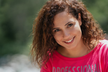 Close up portrait of a cheerful curly young woman smiling outdoors