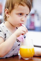 Little beautiful girl child drinks orange. (Vitamins, health, thirst, happy childhood concept)