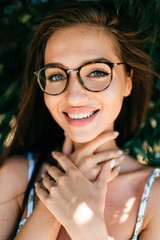 Closeup emotional  lifestyle portrait of adorable beautiful young cheerful coquette fashionable girl in trendy glasses with big natural lips and blue happy eyes smiling outdoor at nature in summer.