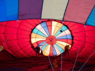 Two People Checking a Hot Air Balloon as it is being inflated for a hot air balloon festival.