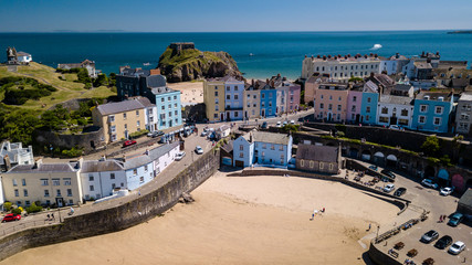 Aerial drone view of colorful buildings next to the ocean in a picturesque seaside town (Tenby, Wales, UK)