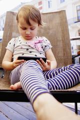 Social Media addiction. Little child girl holding smart phone