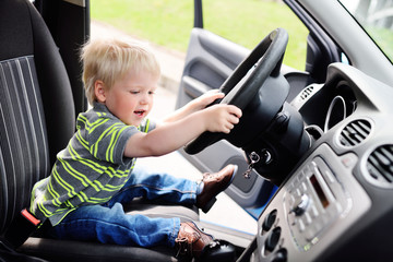 little baby boy turns the steering wheel of the car