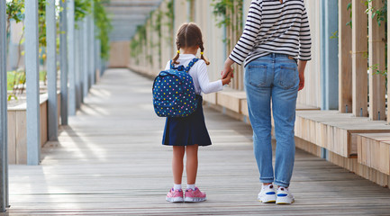 first day at school. mother leads  little child school girl in first grade.