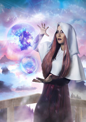 Beautiful sorceress holding two magic spheres on fantasy nature background photo.