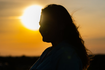 Woman silhouetted in the setting sun.