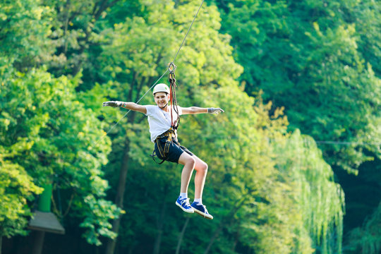 Happy, cute, young boy in white t shirt and helmet having fun and playing at adventure park, holding ropes and climbing wooden stairs. active lifestyle concept