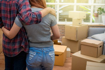 Back side of Asian young couple hugging together over the big cardboard box and sofa when moving in new house, Moving and House Hunting concept