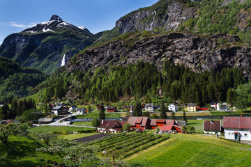 Peaceful Flam Valley with quaint village, waterfall and towering mountains