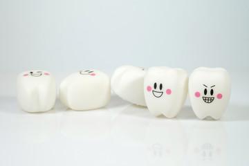 Smiley Plastic teeth toy on a gray background, poor dental care concept, falling teeth