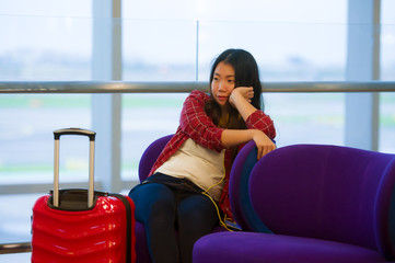 happy and pretty Asian Chinese tourist woman sitting at airport departure boarding gate with suitcase hand luggage waiting for flight on in holidays travel