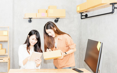 Women are packing products into boxes according to customer orders.Delivery term door to door.Small business owner writing address on cardboard box