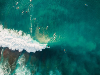 Aerial view of surfers and barrel wave in blue ocean. Surfer on wave. Top view