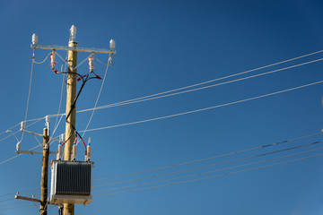 Power poles with power transformer against a blue sky
