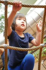 Asian Chinese Child climbing rope obstacle course