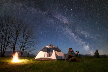 Incredible beautiful night camping in mountains. Young man hiker with photo camera sitting alone in front of tourist tent at burning bonfire on grassy valley under night blue starry sky with Milky way