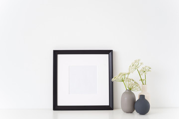 Black portrait square frame mock up with a episcopal weed in little vases. Mockup for quote, promotion, headline, design. Template for small businesses, lifestyle bloggers, social media