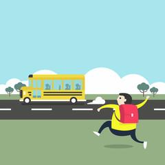 A boy running after a school bus.