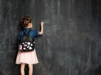 Little girl with school bag near blackboard in classroom.Pupil is writing on a chalkboard in a...