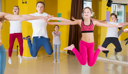 Tweens jumping with female coach in choreography class