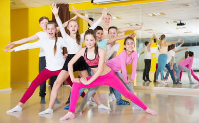 Children having fun in choreography class, posing with trainer