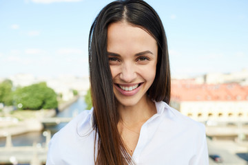Cheerful attractive young woman with black hair wearing blouse smiling at camera while standing against cityscape