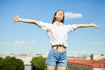 Happy free young woman in white shirt and denim shorts outstretching arms and keeping eyes closed while standing on roof in city, freedom concept