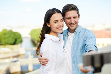 Happy beautiful young couple in casual clothing using monopod while photographing themselves on smartphone, they embracing and standing on roof in city