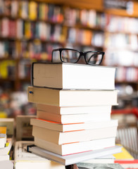 glasses on top of stack of books lying on table in bookstore