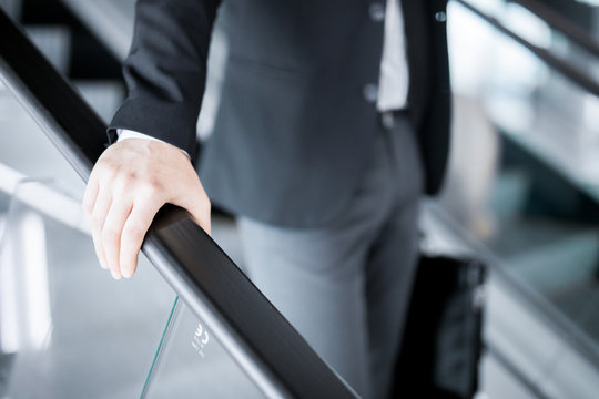 Hand of young businessman on railings of escalator during motion downwards