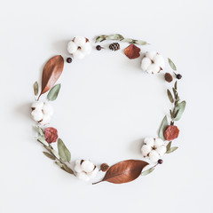 Autumn composition. Wreath made of eucalyptus branches, cotton flowers, dried leaves on pastel gray background. Autumn, fall concept. Flat lay, top view, square