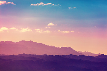 Sunset over mountains. Silhouette of a mountain range against sky at sunset