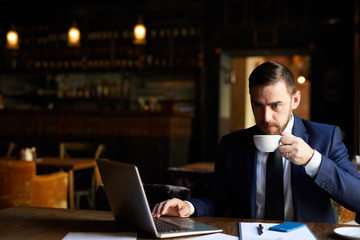 Serious thoughtful handsome bearded businessman in suit working on report and drinking coffee while sitting in empty restaurant