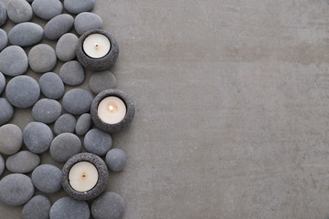 Pile of gray stones with three candle and grey background
