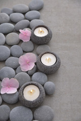 Tuinposter Spa Pile of gray stones with three candle with Pink hydrangea petals and grey background
